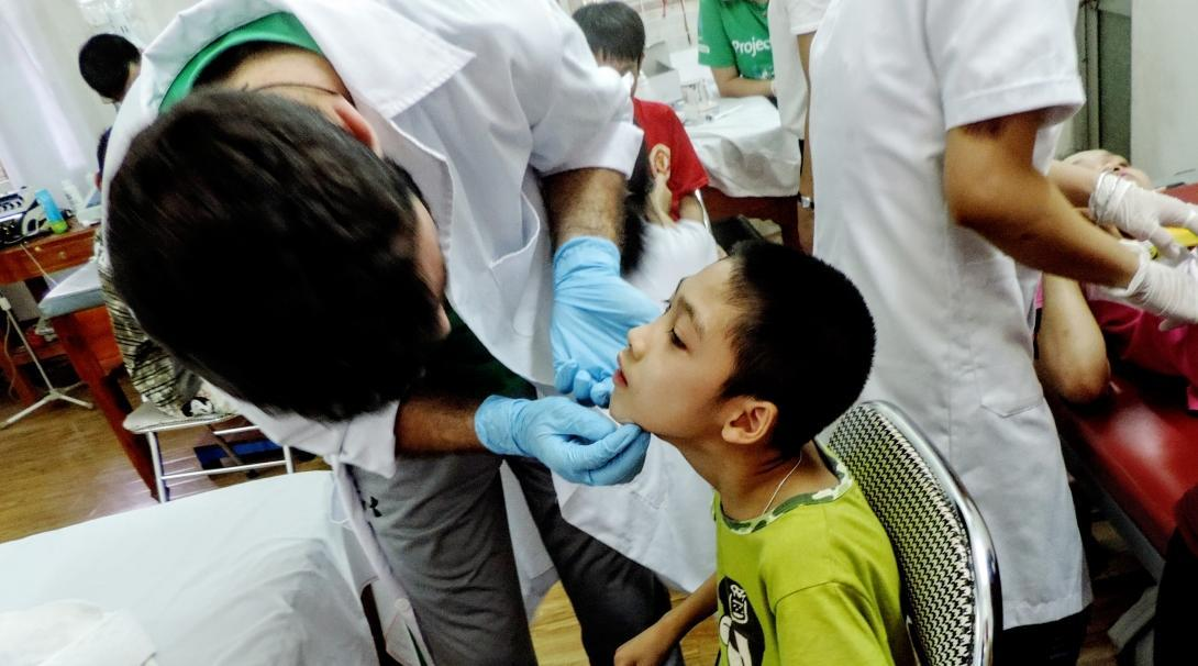 A male intern from Projects Abroad is seen carrrying out an examination on a child as part of his nursing internship in Vietnam.